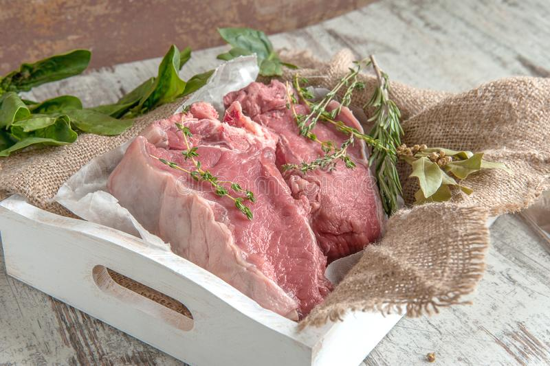 Cuts of beef for grilling on a wooden cutting Board with spinach, rosemary and Provencal herbs for the marinade in a rustic style stock photography