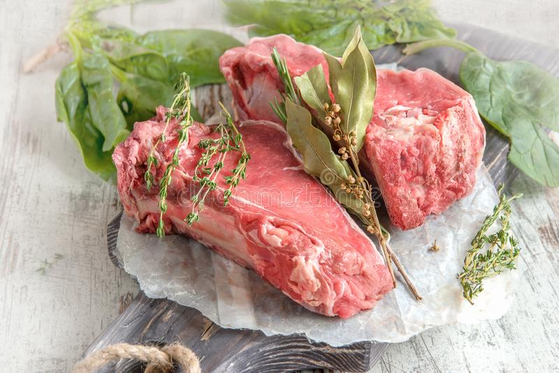 Cuts of beef for grilling on a wooden cutting Board with spinach, rosemary and Provencal herbs for the marinade in a rustic style royalty free stock photo