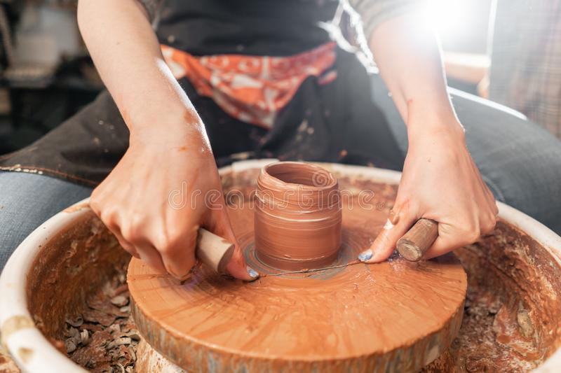 Cuts of product with wire. Craftsman hands making pottery bowl. Woman working on potter wheel . Family business shop. Happy woman working on potter wheel in royalty free stock photos