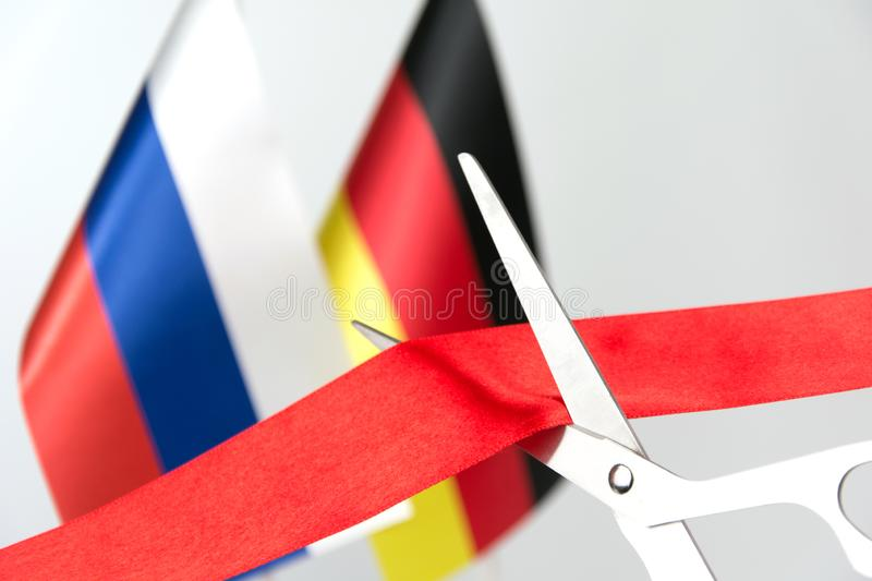Cuts ribbon project russia germany flag. Cuts ribbon project completed russia germany flag North European Gas Pipeline blurred background royalty free stock photography