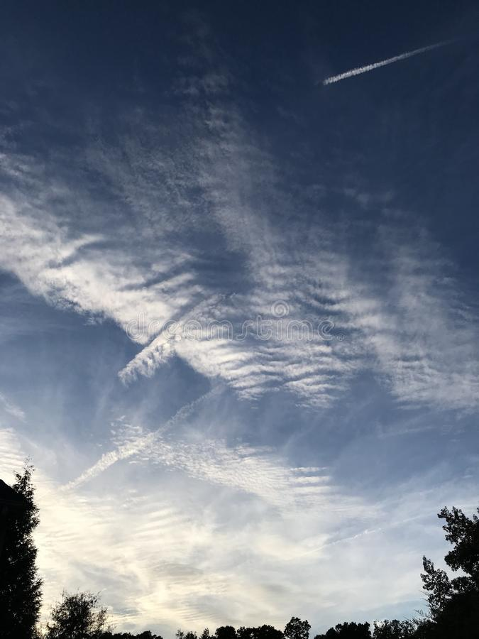 Stratus Clouds Vapor Trails Cuts Right Through. Layers of tufted stratus clouds with reverse vapor trails cutting through them like soft butter royalty free stock images