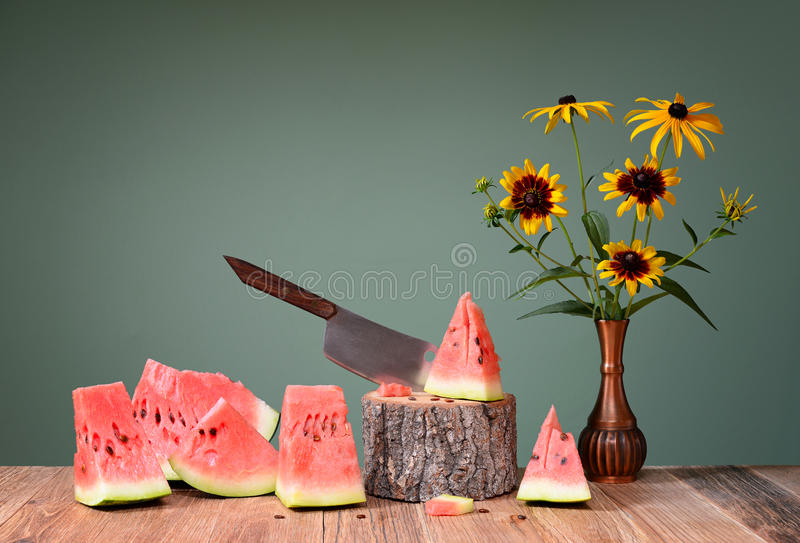 Cutted watermelon and flowers in metal vase stock photos