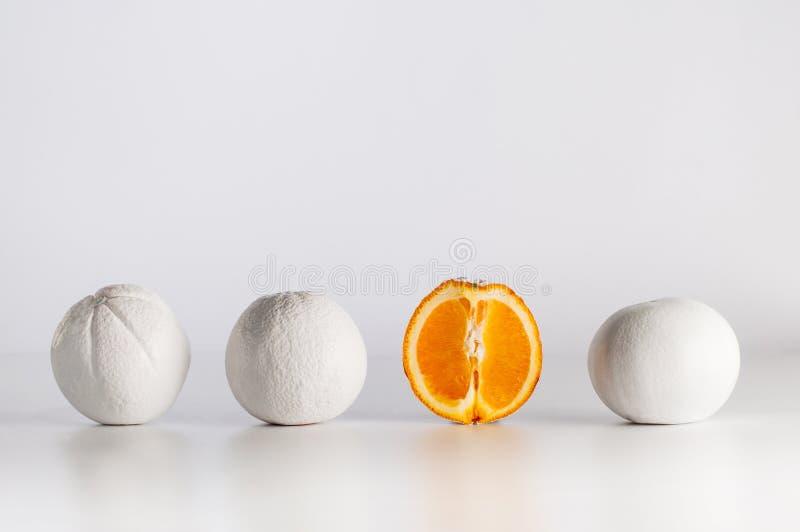 Cutted оранжевое около белых покрашенных апельсинов в ряд на светлой предпосылке стоковые изображения