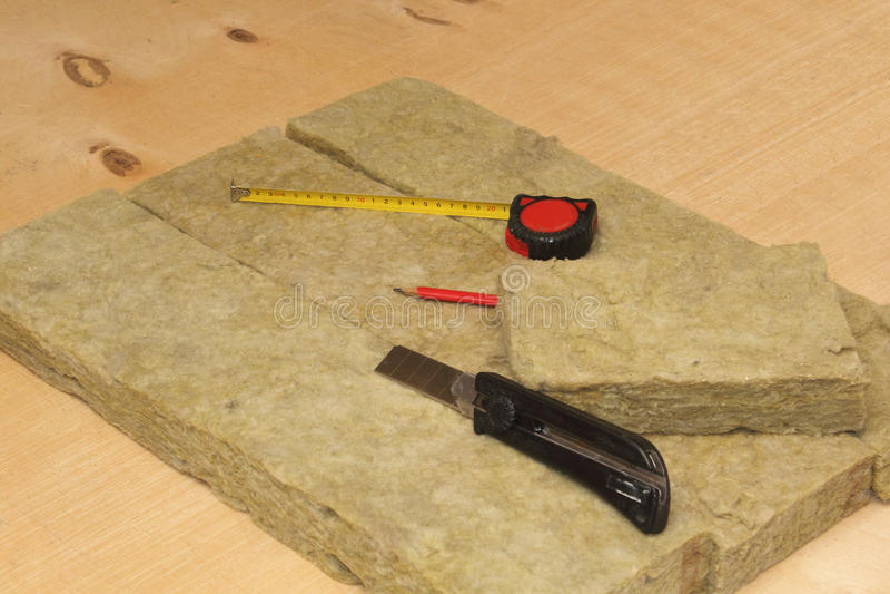 Cutted mineralisk ull, kniv, blyertspenna och måttband royaltyfria bilder