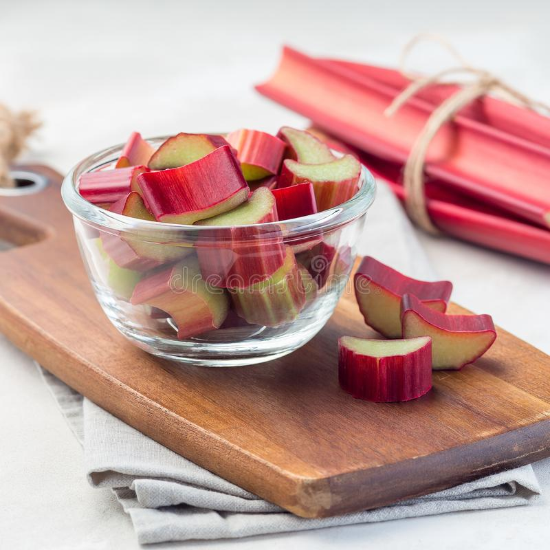 Cutted rhubarb in a glass dish and on a wooden board, square stock photos