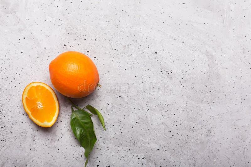 Cutted und ganze Orangen auf dem grauen Hintergrund, Draufsicht stockfoto