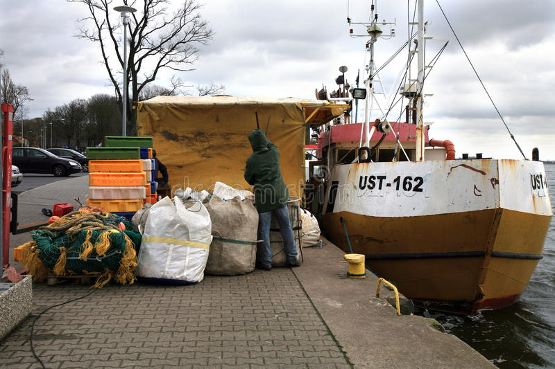 Cutter after fishing by dark, stormy day. stock photos