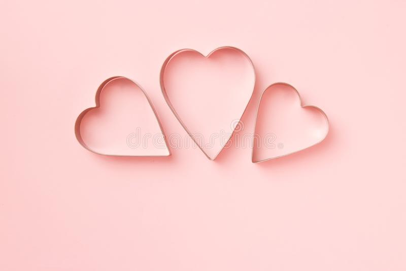 3 cutters cookies in heart shape on pastel pink background. Concept Valentine`s card. Top view, copy space for text stock images