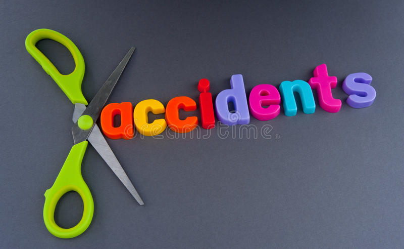 Cutting accidents. Text ' accidents ' in colorful lower case letters with a pair of scissors , concept of cutting, dark background royalty free stock photography