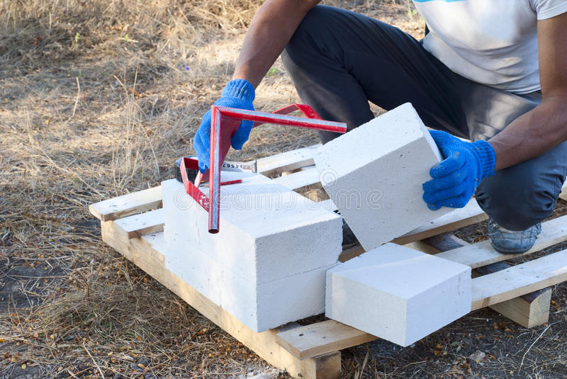 Cutting aerated concrete. Builder cut into pieces aerated concrete block royalty free stock image