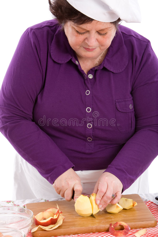 Cutting the apple. Female chef busy cutting an apple in half stock image