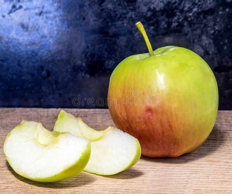 Cutting apple on a board royalty free stock photography