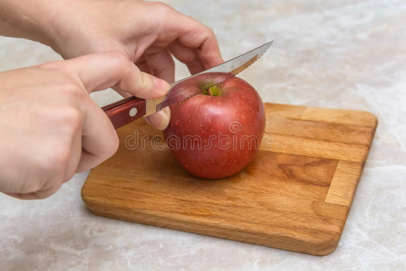Cutting apple into halfs. Slicing red apple with knife into pieces stock photography