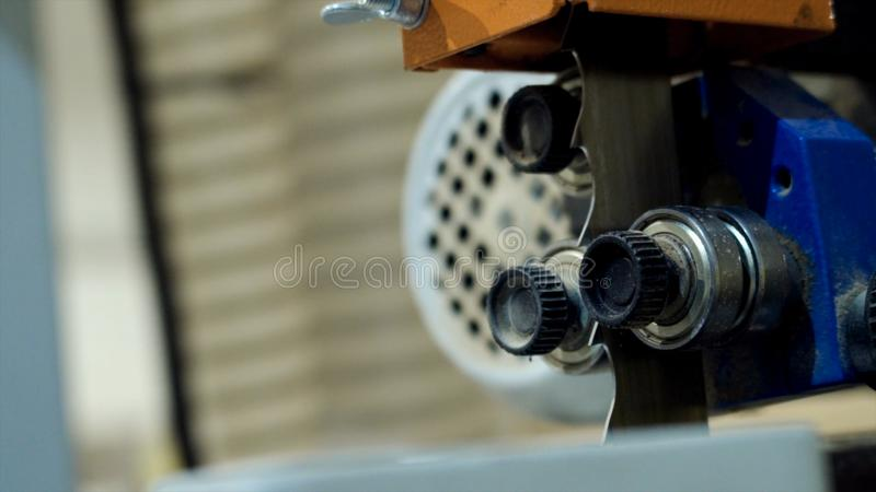 Cutting band saw machine at woodworking plant. Action. Close-up of professional band saw machine in motion before stock photos
