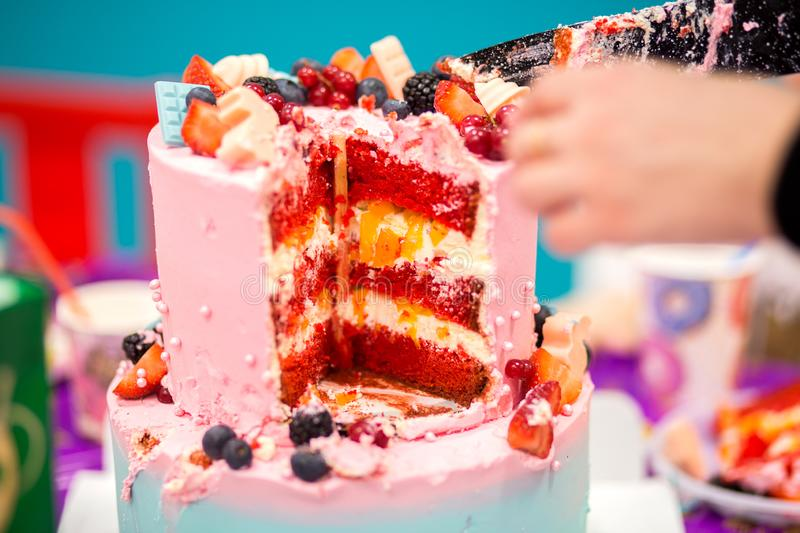 Cutting of beautiful festive pink cake. Puff cake for a birthday in a section royalty free stock photography