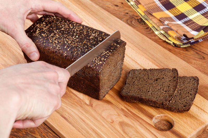 Cutting Black Bread royalty free stock photo