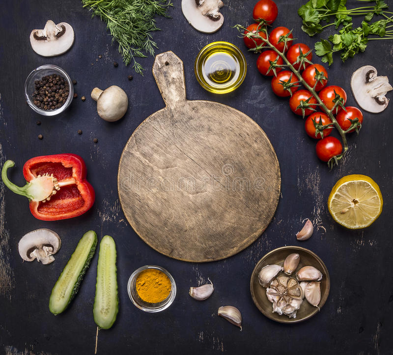 Cutting board, around lie ingredients variety of vegetables and fruits, place for text,frame wooden rustic background top view stock photography