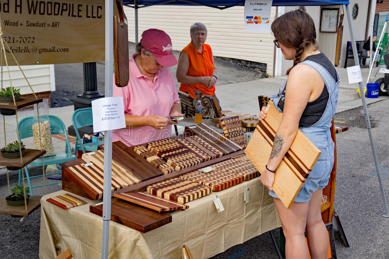 Cutting Board Artist at the Vinton Dogwood Festival. Vinton, VA – April 29th: Young woman purchasing a handmade cutting board at the Annual Dogwood stock image