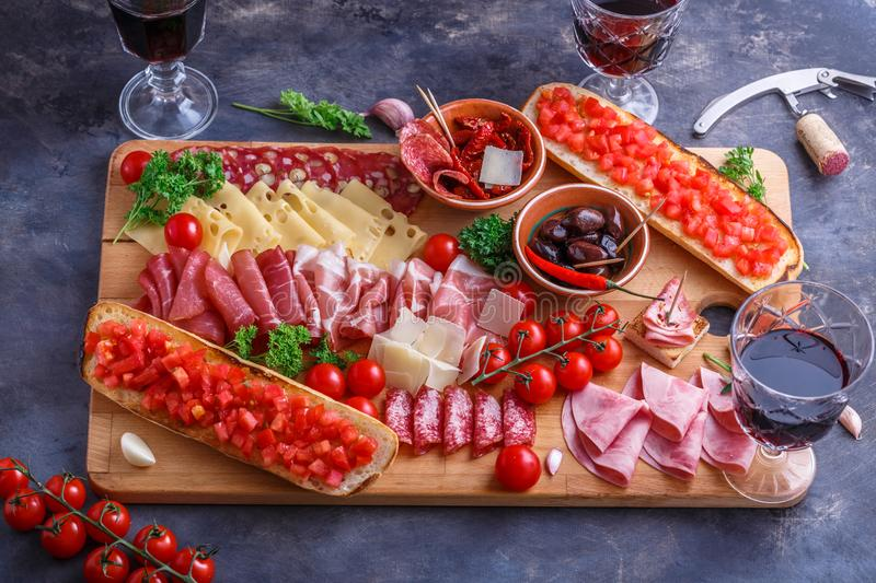 Cutting board of Assorted Cured Meats, Cheese, bread and wine.  royalty free stock photos