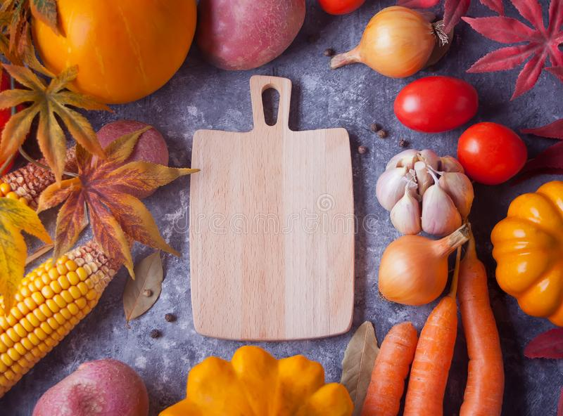 Cutting board, autumn leaves, vegetables on the black background. Autumn harvest. Autumn food. Top view. Copy space stock photography