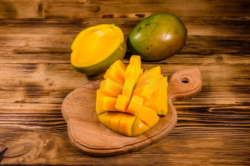 Cutting board with chopped mango fruit on a wooden table royalty free stock photography