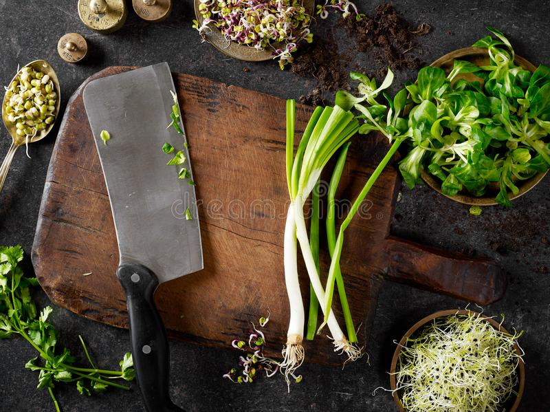 Cutting board, cleaver and greens stock photography