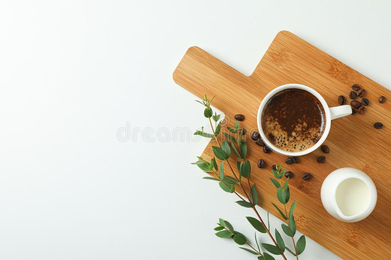 Cutting board with cup of fresh coffee, milk, coffee beans and plant branch on white background, space for text. And top view royalty free stock photo