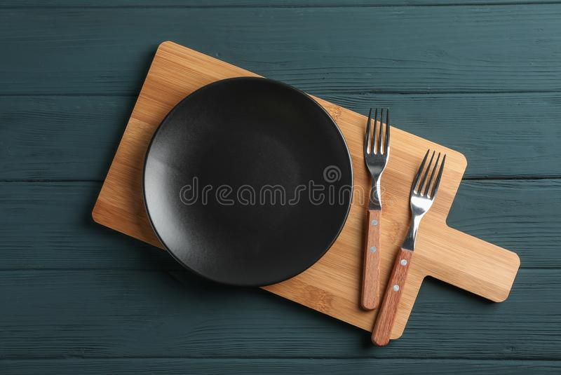 Cutting board and cutlery on wooden background stock photography
