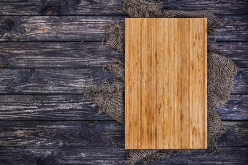 Cutting board on dark wood background, top view stock images