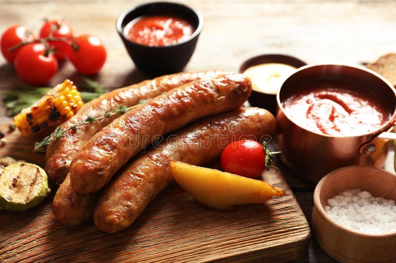 Cutting board with delicious barbecued sausages served. On wooden table stock image