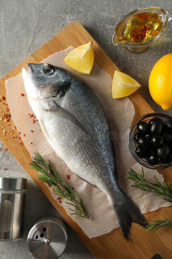 Cutting board with Dorado fish and cooking ingredients on background, top view royalty free stock photo
