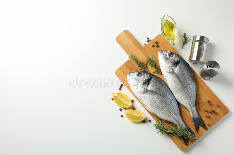 Cutting board with Dorado fishes and cooking ingredients on background, top view. Cutting board with Dorado fishes and cooking ingredients on white background stock image
