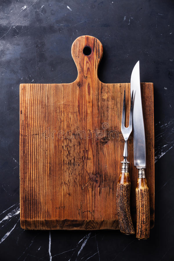 Cutting board and fork and knife carving set stock photos