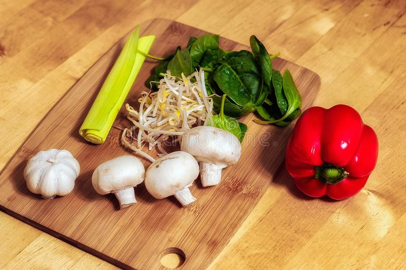 Cutting board with mushrooms and vegetables royalty free stock image