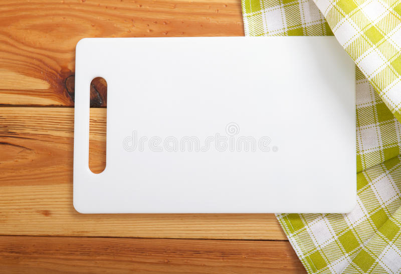 Cutting board over towel on wooden kitchen table. Top view stock photo