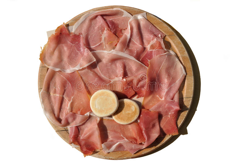 Cutting board with parma's ham. Outlined cutting board filled with slices of parma-ham in sunny light royalty free stock image