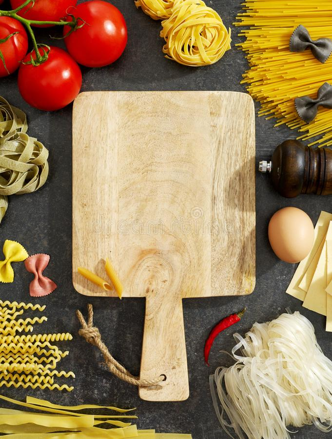 Cutting board, pasta and ingredients stock photos