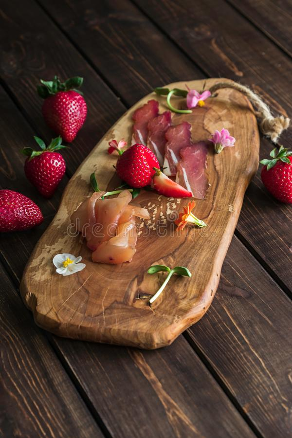 Cutting board with prosciutto, bacon and strawberries on wooden background. Meat platter appetizer royalty free stock image