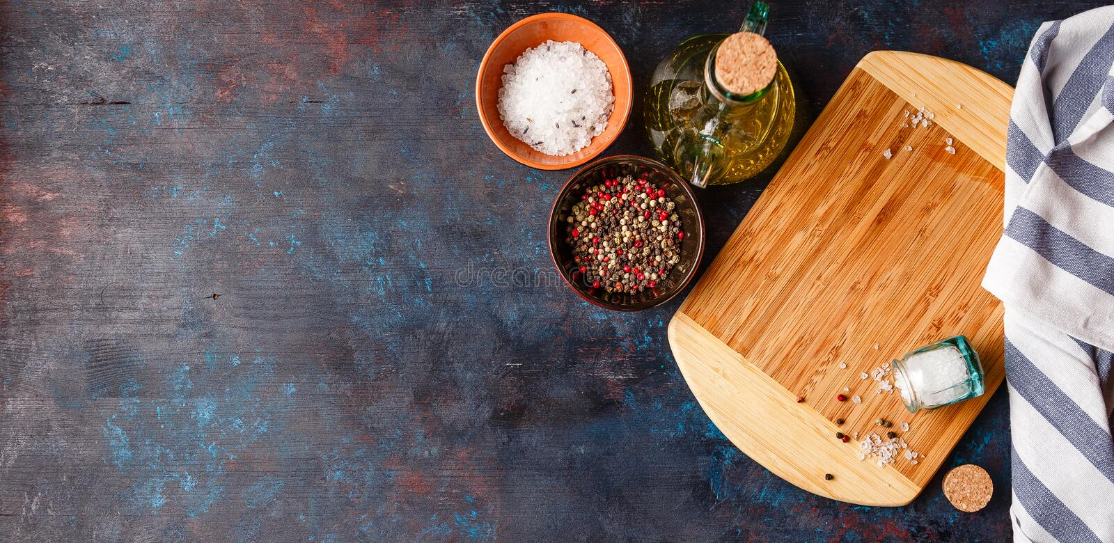 Cutting Board on table. Cutting Board, olive oil, salt and pepper on dark table royalty free stock photography