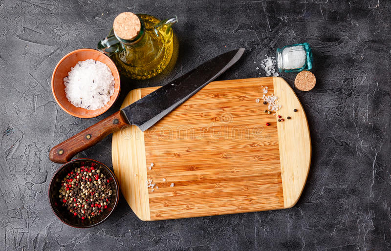 Cutting Board on table. Cutting Board, olive oil, salt, pepper and knife on dark table royalty free stock photography