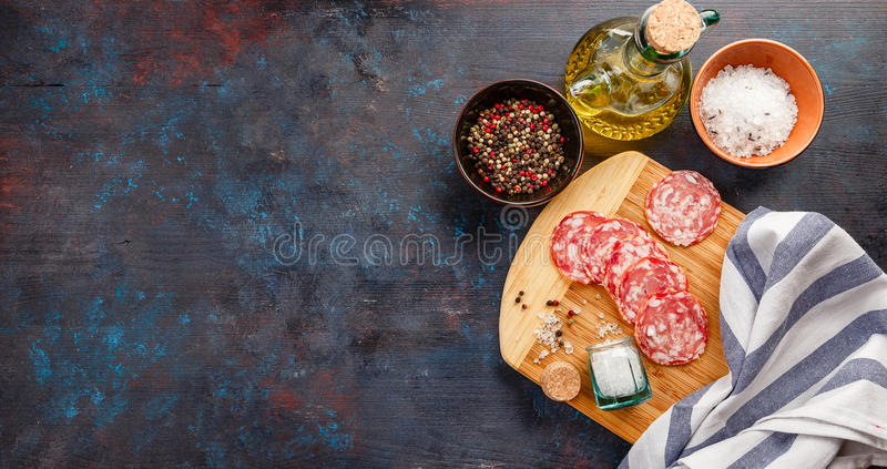 Cutting Board on table. Wooden cutting board, olive oil, salt, pepper and pieces of Salchichon on dark table royalty free stock images