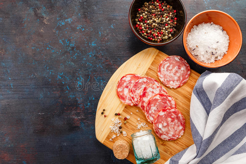 Cutting Board on table. Wooden cutting board, salt, pepper and pieces of Salchichon on dark table stock photography