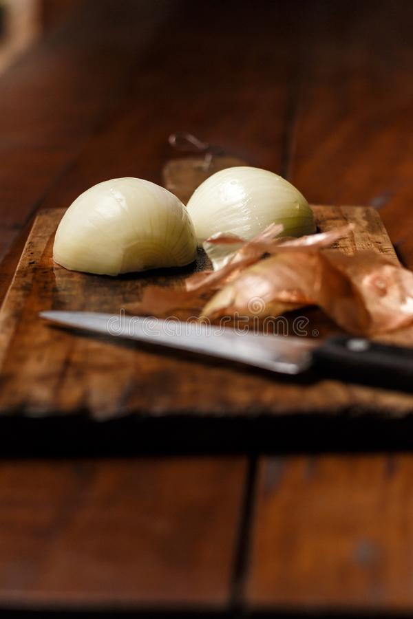 Cutting board on top of rustic wooden table. Knife in the foreground and onion cut in half as the main subject. royalty free stock image