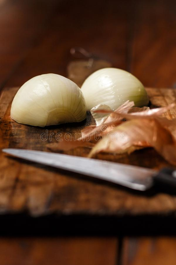 Cutting board on top of rustic wooden table. Onion cut into half knife in the foreground and onion peels. royalty free stock photo