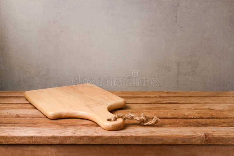 Cutting board on wooden deck table over rustic wall background. Cooking. Concept royalty free stock photography