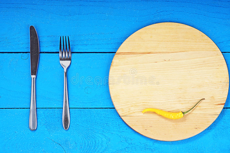 Cutting board with yellow pepper, fork and knife royalty free stock photography