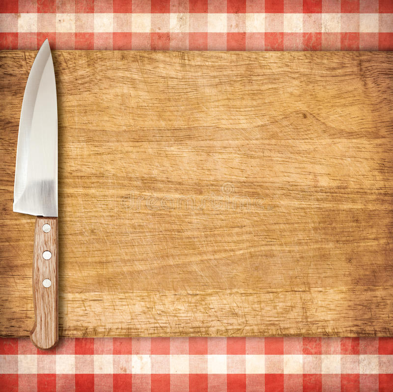 Cutting breadboard and knife over red grunge gingham tablecloth. Background stock photo