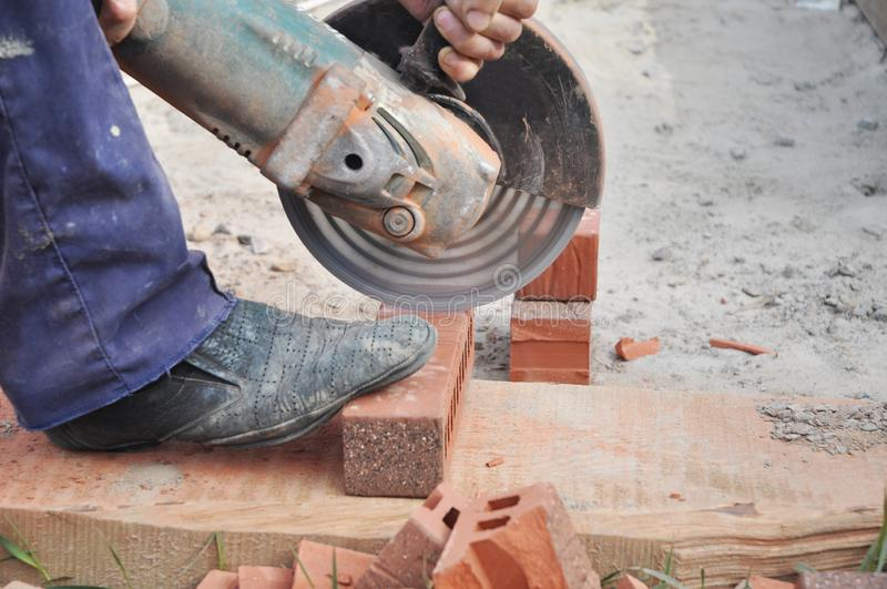 Cutting Brick with a Diamond Saw. Masonry Cutting. Contractor Cut a Brick With a Wet Saw. Circular saw is a power-saw with disk. Photo royalty free stock photo