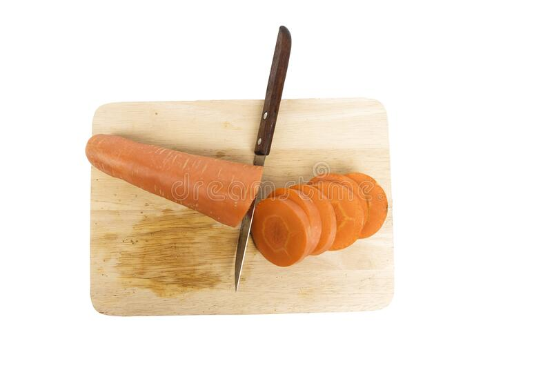 Cutting carrot into small pieces on a wooden chopping board and isolated over a white background. Added clipping path stock photo