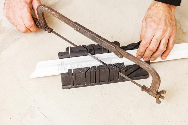 Cutting ceiling skirting in miter box. Cutting ceiling moldings in miter box closeup stock image